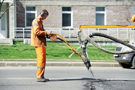 multilayered: Road worker at asphalt roadway street patching reparing work Stock Photo