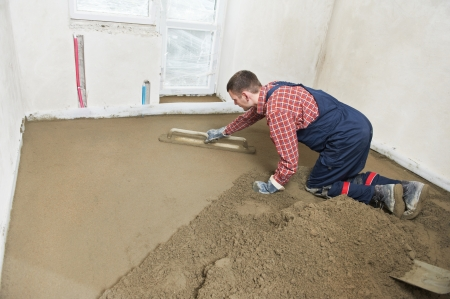 Plasterer at indoor concrete cement floor topping with float photo