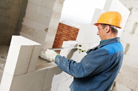 cement solution: construction mason worker bricklayer installing calcium silicate brick during indoor wall creation