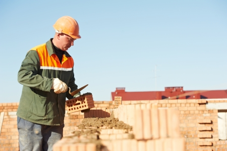 cement solution: construction mason worker bricklayer installing red brick with trowel putty knife outdoors Stock Photo