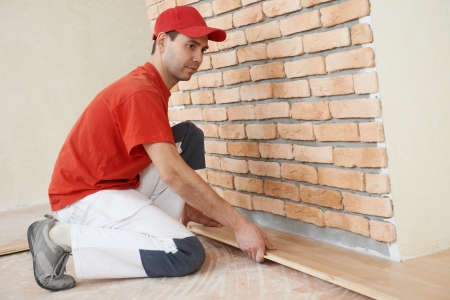 tongue and groove: carpenter worker installing wood parquet board during flooring work