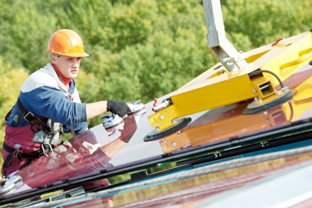double glazing: Tho builders worker installing glass windows on facade of business building