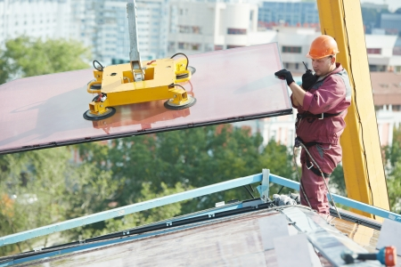 vented: Tho builders worker installing glass windows on facade of business building
