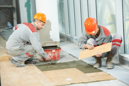 Two industrial tiler builder worker installing floor tile at repair renovation work photo
