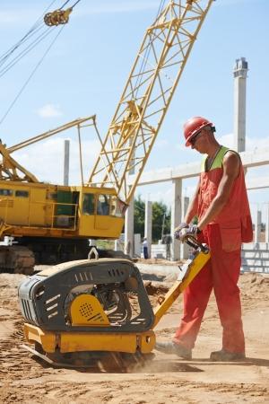 vibration machine: builder worker compacting soil with vibration plate compaction machine during pavement roadwork