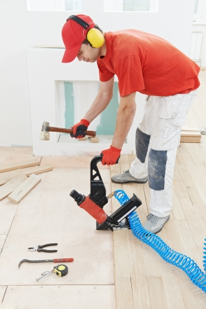 carpenter worker installing wood floor parquet board during flooring work with hammer photo