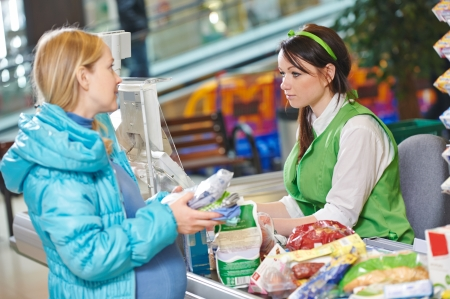customer assistant: Customer buying food at supermarket and making check out with cashdesk worker in store Stock Photo