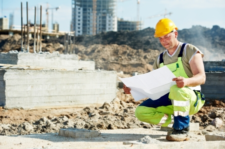 taskmaster: One engineer builder with blueprint plan draft at construction site