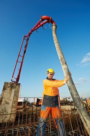 builder worker standing near trailer-mounted boom concrete pump on metal rods reinforcement of concrete casting formwork Stock Photo - 24711661