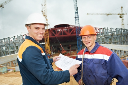 Two engineer builders with blueprint plan at construction site photo