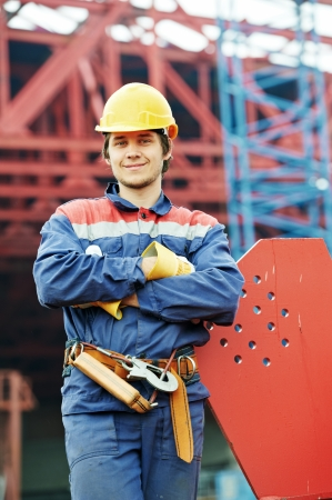 foremaster: builder worker in uniform and safety protective equipment at construction site in front of metal construction frames Stock Photo