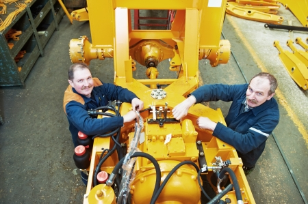 mechanician: adult experienced industrial workers during heavy industry machinery assembling on production line manufacturing workshop
