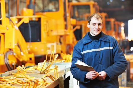 Portrait of young adult experienced industrial engineer over heavy industry machinery production line manufacturing workshop photo