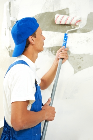 priming: One painter with paint roller making wall prime coating  at home repair renovation work Stock Photo