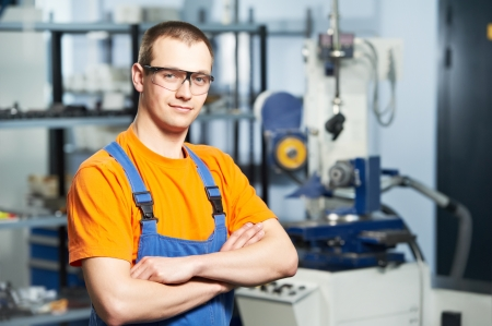 産業機械生産ライン製造ワーク ショップ上の若い大人経験豊富な工業労働者の肖像画
