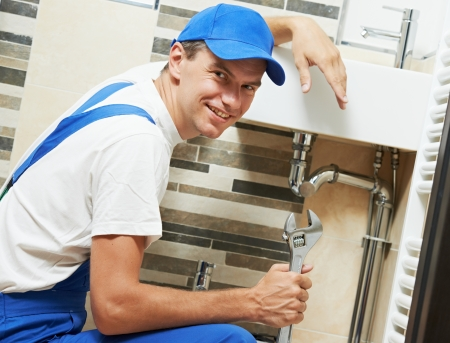 Young happy plumber worker with spanner at sanitary washbasin installation system photo