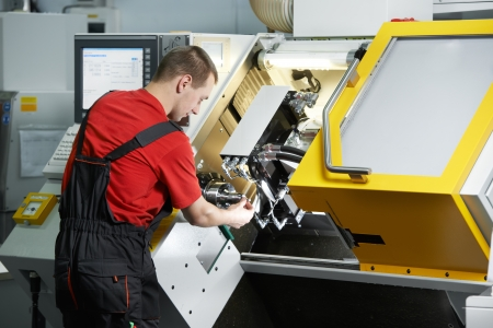 fettler: mechanical technician worker working at cnc milling machine center in tool workshop Stock Photo