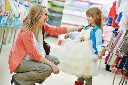 stores: vrouw en meisje kiezen en proberen op kleding tijdens het winkelen bij kledingstuk supermarkt Stockfoto