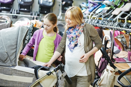 shopping buggy: Young pregnant woman choosing baby carriage or pram buggy for newborn at shop store