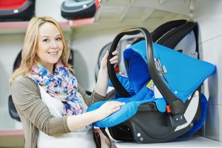 car seat: donna che sceglie seggiolino auto per neonato in negozio supermercato Archivio Fotografico