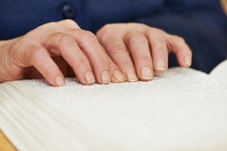 braille: Libro de lectura de manos de la mujer ciega o deficiente visual escrito en Braille