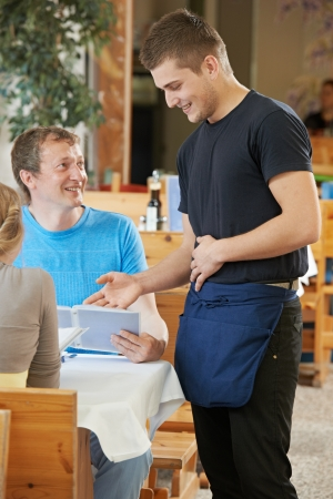 advising: waiter ready to serving or order in small italian restaurant