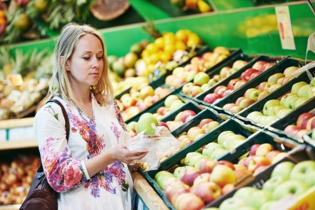 Woman choosing bio food fruit apple in vegetable supermarket during shopping photo