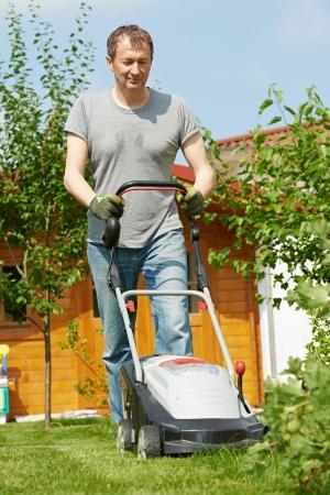 grassy plot: man cutting grass in his garden yard with lawn mower