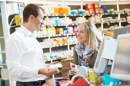 drug store: cheerful pharmacist chemist man worker standing at pharmacy drugstore desk with colleague