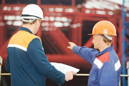 directing: Two engineer builders with blueprint plan at construction site Stock Photo