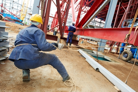 millwright: builder worker in uniform at construction site installing metal construction frames