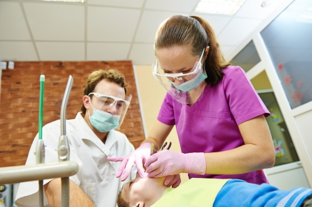 curing: child dentist treat boy teeth under sedation with dental curing ultraviolet light equipment Stock Photo