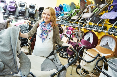 stroller: Young pregnant woman choosing baby carriage or pram buggy for newborn at shop store