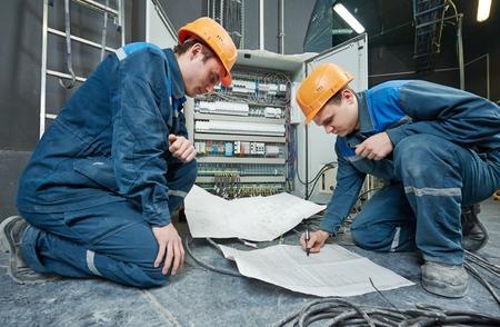 alba�il: dos constructor ingeniero electricista con proyecto esquema de impresi�n azul delante de la caja de interruptores de fusibles
