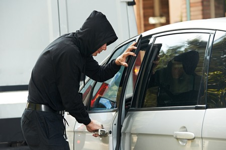 Thief stealing automobile car at daylight street in city photo