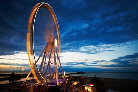 Amusement park at night - ferris wheel and rollercoaster in motion photo