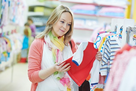 Young pregnant woman choosing newborn clothes at baby shop store Stock Photo