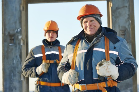millwright: Team of builder worker in safety protective equipment at winter construction site