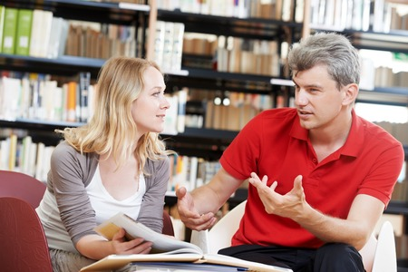 Two young adult peoples reading discussing book in a library Stock Photo - 27913933