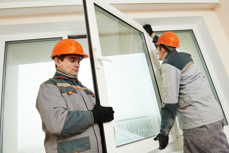 craftsman: Dos hombres trabajadores de constructores industriales en instalación de la ventana