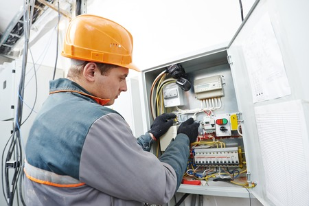 Young adult electrician builder engineer screwing equipment in fuse box photo
