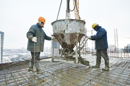 formwork: construction building workers at construction site pouring concrete in form