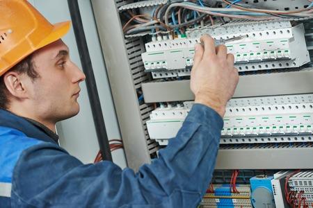 electricidad industrial: Los jóvenes adultos de ingeniero constructor electricista equipo atornillar la caja de fusibles