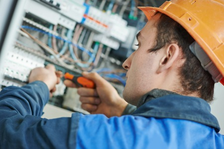 electrical safety: Young adult electrician builder engineer screwing equipment in fuse box