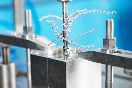 machining: Close up machining tool drill during metal cutting process boring a hole Stock Photo