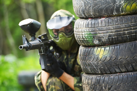 paintball player in protective uniform and mask aiming marker gun in summer