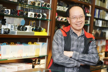 selling service: Assistant seller help buyer by demonstrating digital photo camera at shop store Stock Photo