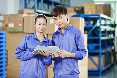 warehousing: two young chinese workers in uniform at warehousing