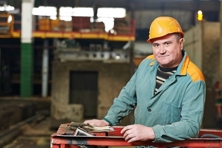 metalworker: portrait of positive adult industrial worker at factory workshop Stock Photo