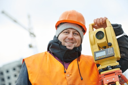 tachymeter: surveyor worker portrait with theodolite transit equipment at road construction site outdoors